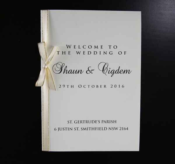 Cream wedding ceremony book with gold and cream ribbon and bow.