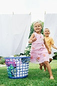 Brother and his sister running under a clothesline
