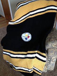 "Loom knit a toasty warm Steelers blanket for the favorite fan in your life! This blanket is knit as a flat panel over 124 pegs of a Serenity Loom (purchased from Hobby Lobby). If you don't have a Serenity Loom, the blanket can be knit on any loom whose pegs are spaced about 3/4"" apart."
