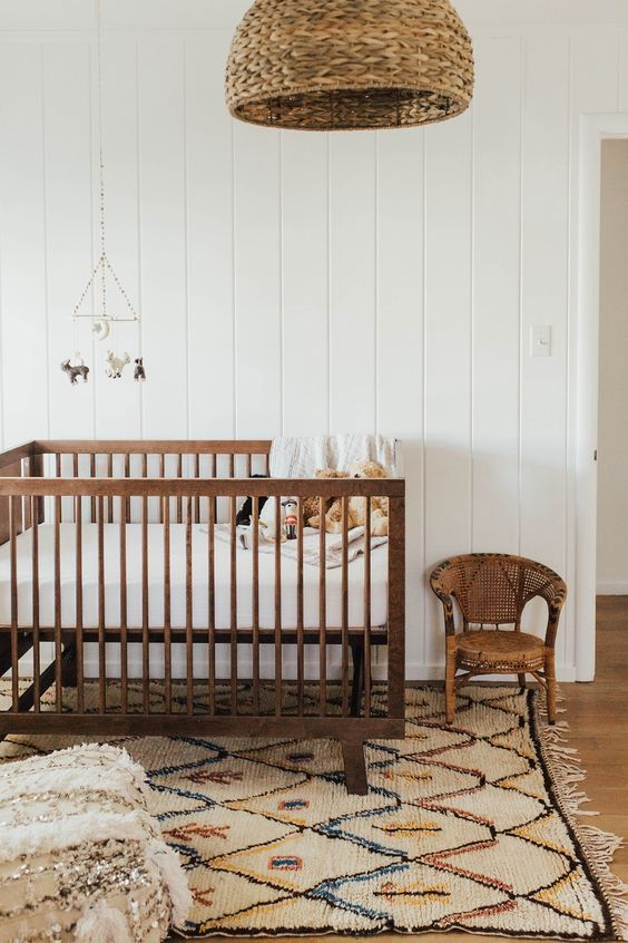 Rustic modern baby nursery design with a white, beige and brown color palette and a touch of global style featuring a woven rattan pendant light, stained wood crib, wicker child's chair, Moroccan textile covered pouf, and a Moroccan area rug - Unique Nursery Ideas & Decor
