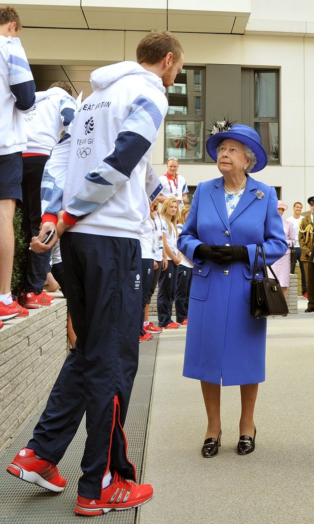 LONDON, UNITED KINGDOM - JULY 28: Queen Elizabeth Il meets one of the taller members of the Great Britain team during a tour of the Athletes Village on day one of the London 2012 Olympics Games on July 28, 2012 in London, England. (Photo by John Stillwell/WPA Pool/Getty Images)