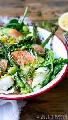 Powersalade met gerookte zalm en gekookte eitjes - 50 gram gerookte zalm in kleine stukjes | 2 eitjes | Handje spinazie | 50 gram spelt | 10 groene aspergetips, uiteinden verwijderd | 1/2 avocado, in dunne plakjes | Handje sojaboontjes | Tuinkers | Olijfolie | Sap van 1 citroen | Peper en zout