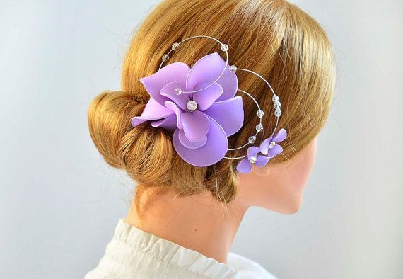 This is an elegant lilac headpiece which is made out of netting and silver hand shaped wire accentuated with flowers and Swarovski crystals. Headpiece