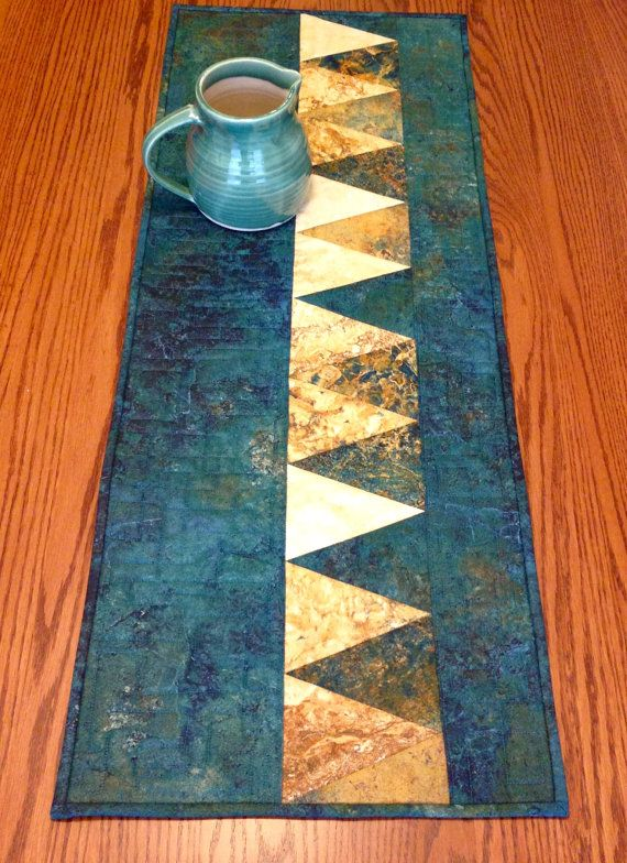 Bold graphic appeal with triangles running down one side of this all cotton table runner. Teal, copper, gold, cream. Quilted with freehand angular square design. Back is a tan solid. 41 x 16. Machine wash and dry.  Ordering is easy. Just click the add to cart button on the right and purchase with a credit card or PayPal and I'll have your table runner on the way in no time