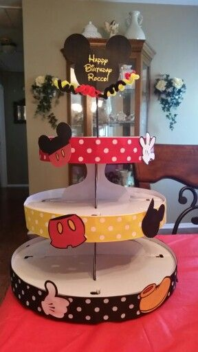 Mickey Mouse cupcake stand. Purchased Wilton cardboard stand from Walmart for $6. Glued ribbon and Mickey clip art I downloaded online. For the top I glued Mickey head to wooded skewer and stuck thru the top and added come curly pipe cleaners.