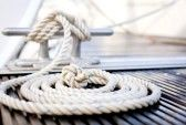 : Close-up of mooring rope with a knotted end tied around a cleat on a wooden pier. Stock Photo