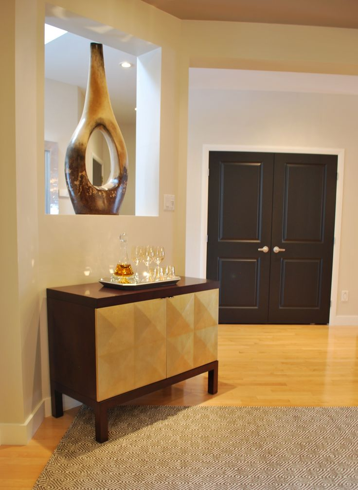 This large sculptural vase makes a dramatic statement in this see through niche. A bench was placed on one side of the niche while this golden bar cabinet we placed on the other side. Black paint was carried onto the double door closet for more drama!