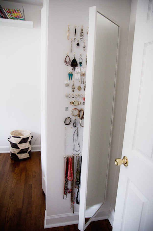 Utilize the space behind a full-length mirror to store jewelry.