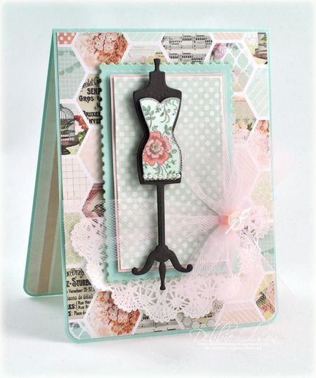 """by Debbie Olson.  JustRight stamps: Ooh La La French Frills/ Spellbinders French Frills dies. Paper: MME: Be Happy 6x6.  Ink: Memento London Fog. Spellbinders: A-2 Francy Postage Sta,[s. A-2 Matting Basics B.  Copics: R20, R22, BG10, YG60, Mint Spica Glitter Pen. Extras: 6"""" pink tulle, pearls trim, paper lace doily, white button/ twine."""