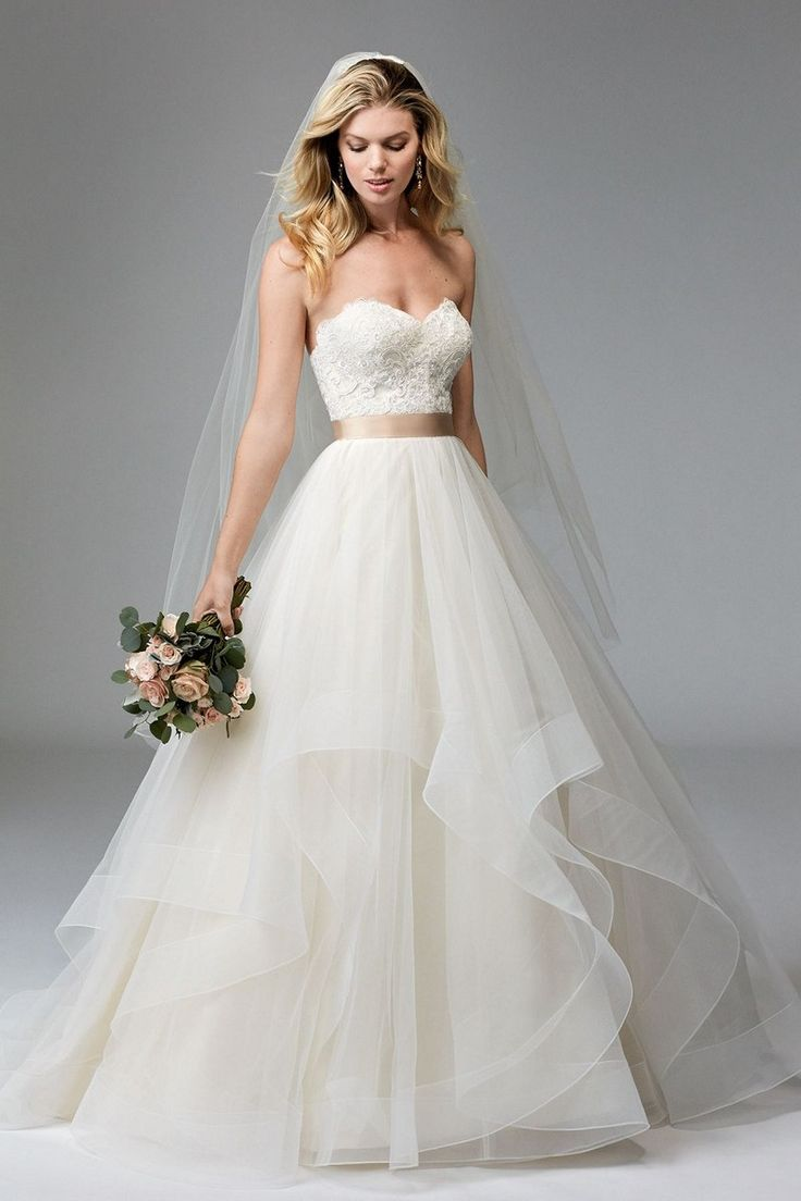 Lace adorns the strapless bodice of this WTOO 17713 Rowena tulle wedding dress, with a scalloped edged sweetheart neckline and semi-open back. The waistline is cinched with a satin ribbon and the overlapping tiers of the full A-line skirt with sweep train are trimmed with horsehair.