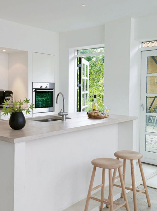 the creamy stone countertop pairs well with the whites and blacks (note the way the edges of the doors are painted—HOT.)
