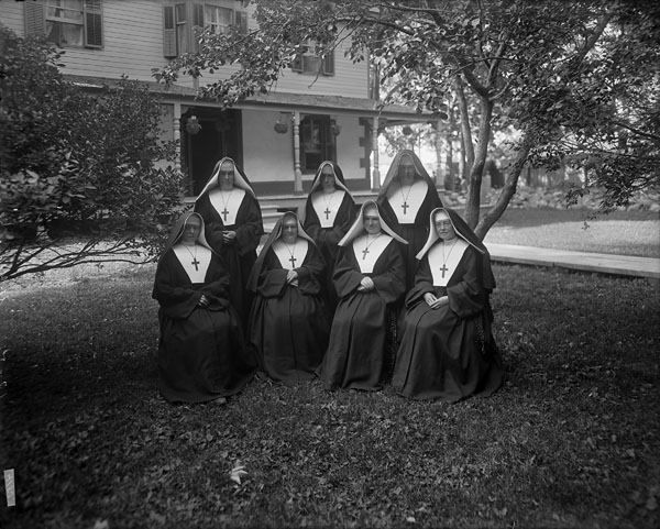 """Nuns of the Sisters of Charity of St. Paul, on the lawn of 1153 Wellington Street in Hintonburg, the site of the St. George's Home for Boys. This """"home"""" was a basically a distribution for boys removed from industrial cities -- and often their families -- in England. The boys would then become indentured labor, mostly on Canadian farms, until they reached the age of 18."""
