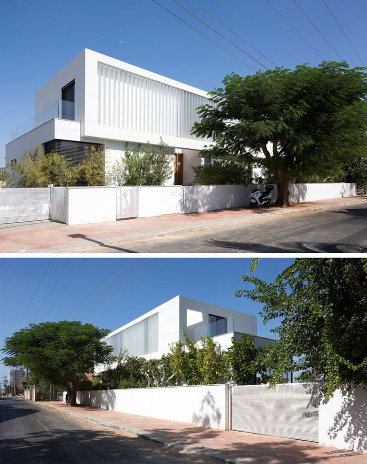 Designed as two separate boxes, one on top of the other, this white modern home has electrical vertical louvers on the top floor that can be easily opened when required.