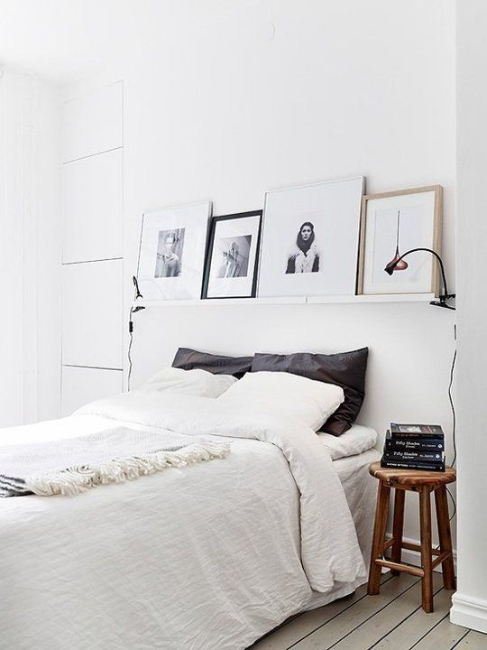 Prints above bed, industrial lamp, exposed wood bedside table, white walls. Liking the dark pillows.