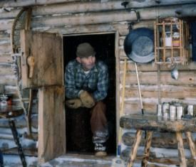 Dick Proenneke standing in the doorway of the cabin he built and lived in for 30 years from the age of 51 to 81 in the wilds of Alaska.