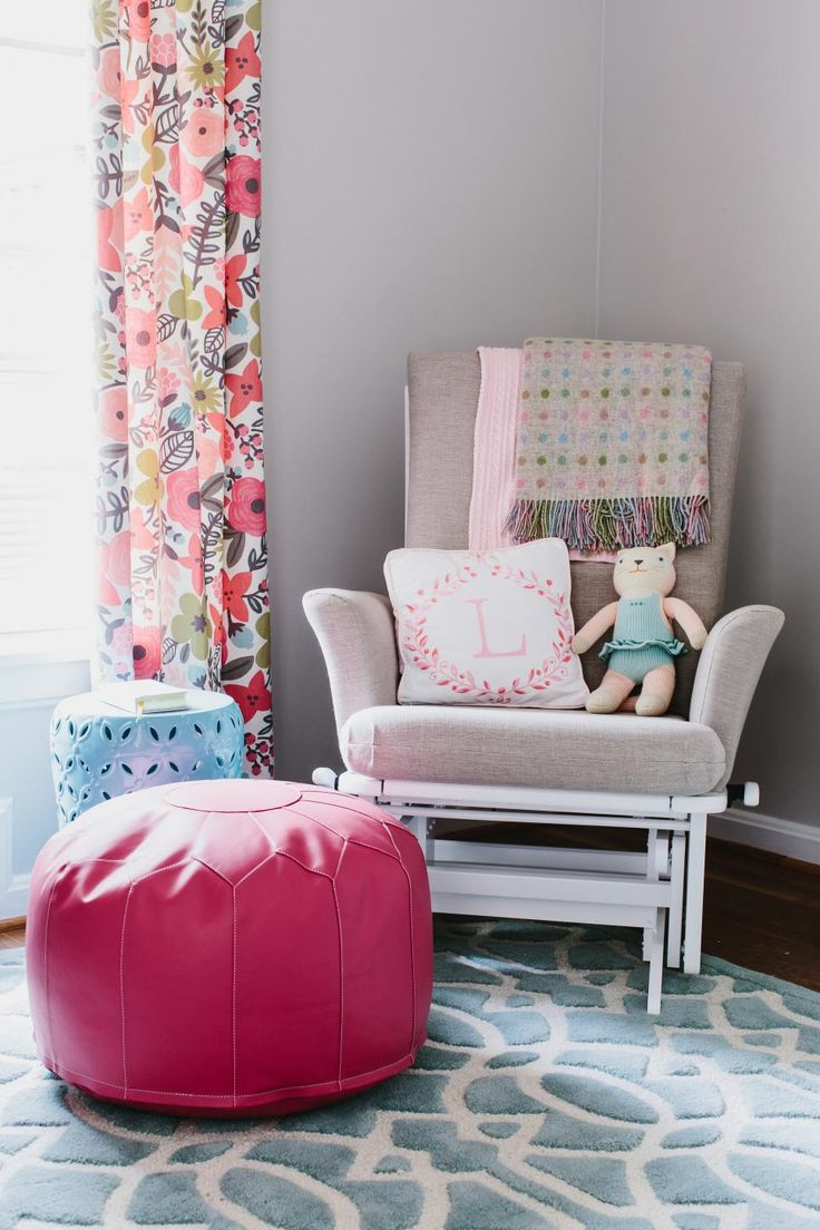 A classic gray glider and stylish hot pink pouf create a cozy corner for relaxing in the soft gray nursery. Floral curtains add a feminine touch and bring out the pink and blue accents in the space.