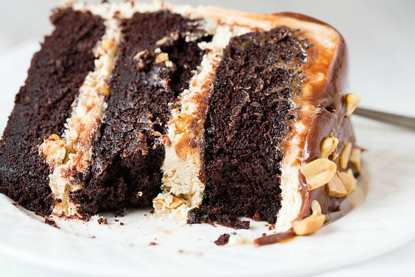Snickers Cake - layers of chocolate cake with peanut nougat filling, covered in salted caramel buttercream and topped with chocolate ganache and chopped peanuts