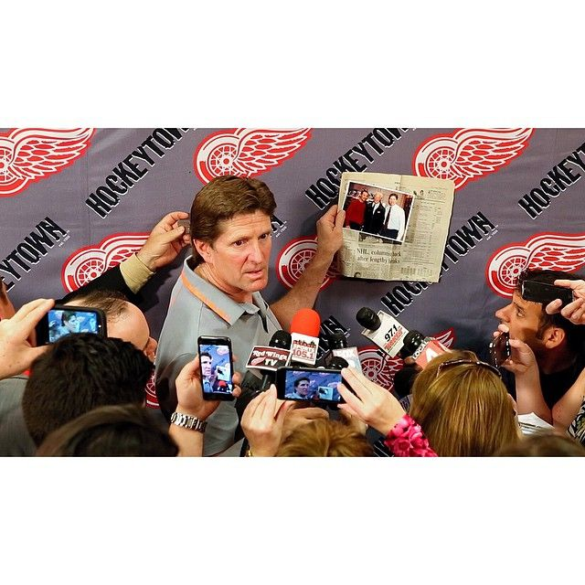 Mike Babcock holds up a picture of him with #RedWings legends Gordie Howe & Steve Yzerman and a newspaper of his first day back in 2005 during his media availability today at The Joe. Link in the bio to watch the highlights of his last time addressing the media from the Red Wings locker room. Good luck in Toronto, Mike. #Babcock