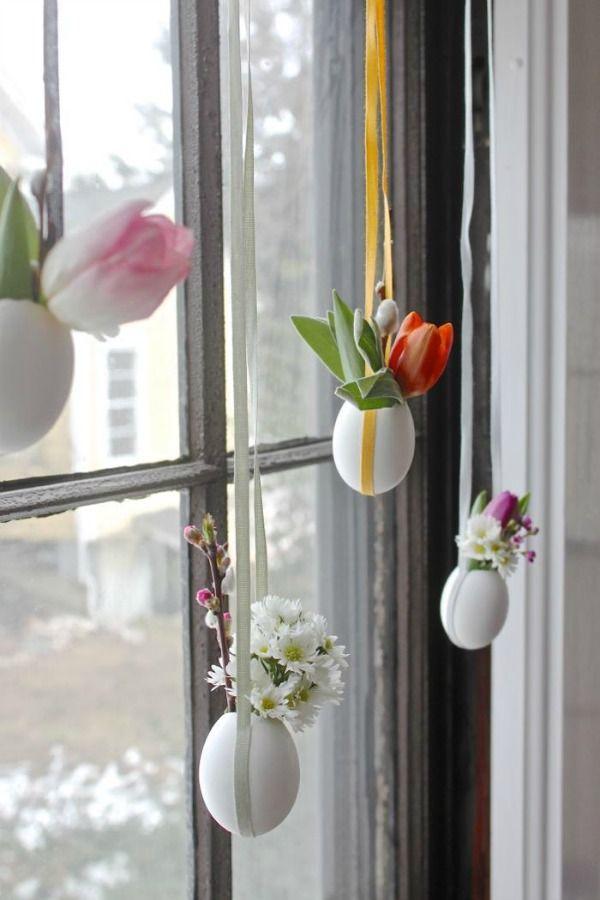 Pasen: eieren als kleine vaasjes met bloemen en paastakjes.