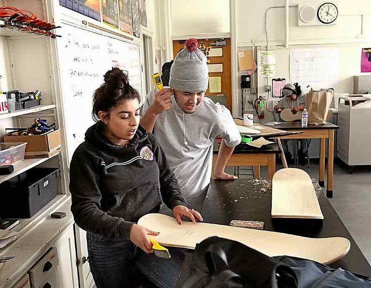 Ryan Escobar takes a look at Maria Escobar's skateboard in Dominic Yarbrough's physical science class at Costanoa High where the students are learning to build their own skateboards. (Dan Coyro -- Santa Cruz Sentinel)