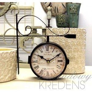 Dwustronny zegar dworcowy retro, na którego tarczy znajdują się francuskie i angielskie napisy.