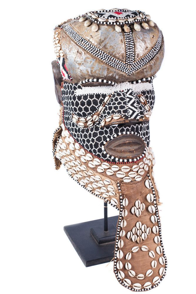 A Congo tribal helmet mask adorned with shells, beading, metal, and burlap. Possibly made by the Kuba people. The Kuba have used more than 20 different types of masks for various functions such as; in