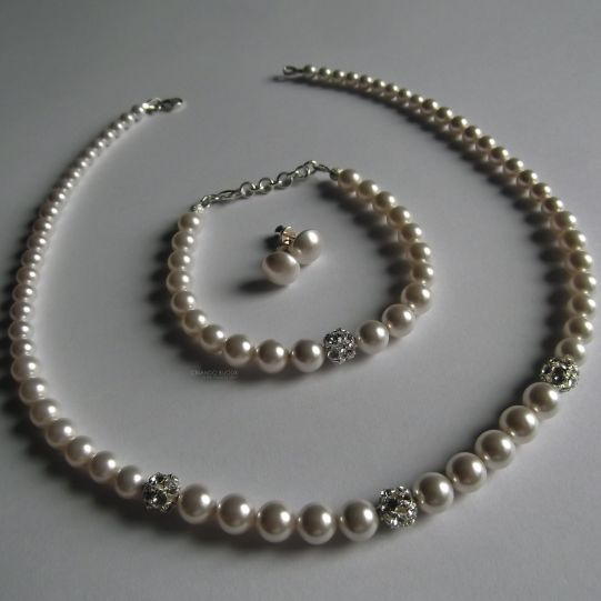 Designed by Criando Bijoux made with SWAROVSKI ELEMENTS.  Culoare perle: alb  Dimensiune perle: 5-8mm Dimensiune globuri de cristal: 3x 8mm  Inchidere colier - argint 925 Inchidere bratara - argint 925 Tortite cercei cu surub - argint 925