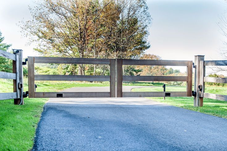 Very clean, simple wooden driveway gate with natural, weathered wood. Designed and installed by Tri State Gate in Westchester County, New York.