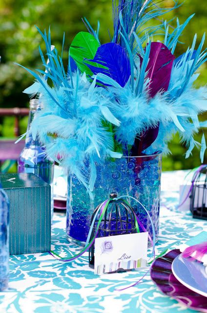 Events That Sparkle: Peacock Feather Tablescape For the smaller centerpieces - layered purple, emerald green, and sapphire blue aqua gems in vases for a striped effect. Vibrant colored peacock feathers and other feathers were arranged in these vases. Striped turquoise and blue candles were also placed on the table.
