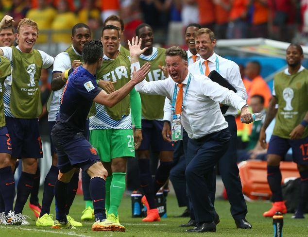 Dutch manager Louis Van Gaal celebrates the Dutch equaliser with Robin Van Persie, who he ...