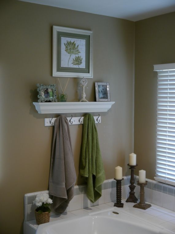 Love the floating shelf or shelves over the bath & towel hooks... Use for pictures or candles. Otherwise wasted space. Great idea. Not the white flowers to the left though. A nice full vase of flowers over by the candles in the Corner by the window would look great. Great wall color. White shutter blinds are good. towels with initials and robe.