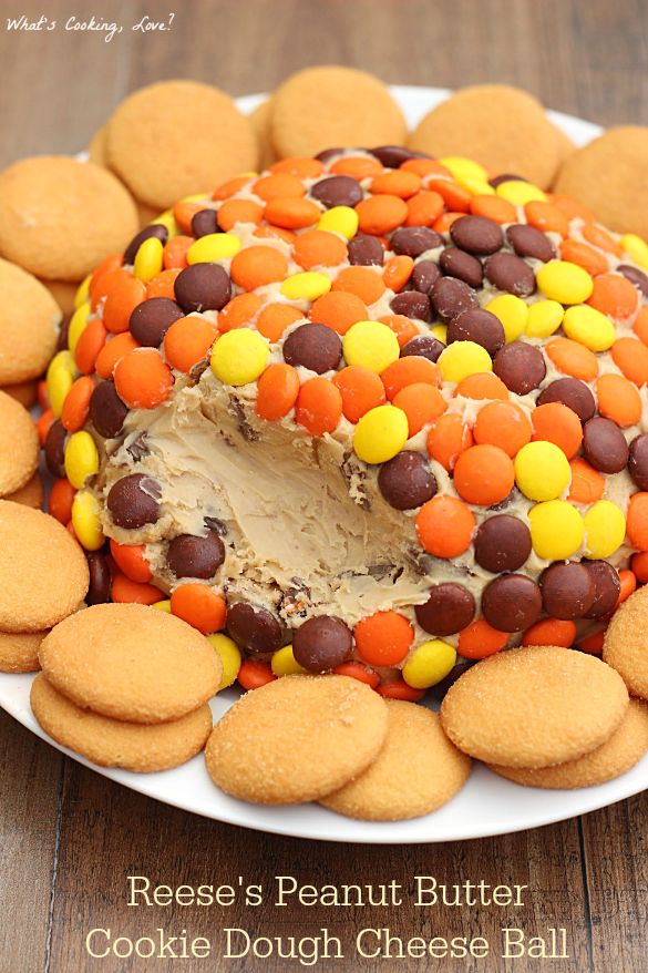 Reese's Peanut Butter Cookie Dough Cheese Ball. A delicious dessert appetizer that tastes like peanut butter cookie dough and is loaded with Reese's Peanut Butter Cups and covered in Reese's Pieces.