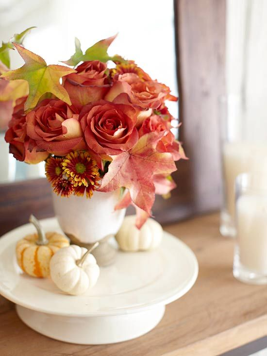 Arrange flowers in pretty fall hues in a vase and tuck in a few autumn leaves. Group several small pumpkins around the vase for a picturesque autumnal arrangement.