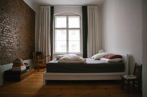 Houten vloer, geschilderde muur en stenen muur, 2 lagen gordijnen in verschillende kleuren.
