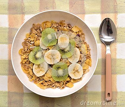 A white bowl of multi grain breakfast cereal topped with slices of  kiwi fruit and banana on a patterned placemat with a spoon at the side.