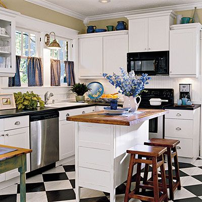 The black and white checkerboard floor and white cabinets. Small Island with wood top. Kitchen is airy and clean. Blue accents and cafe style curtains