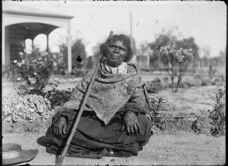 230799PD: Elderly Aboriginal woman wearing European clothing, seated cross-legged in a garden outside a house, Derby, ca. 1898. (Click to Start Zoom)