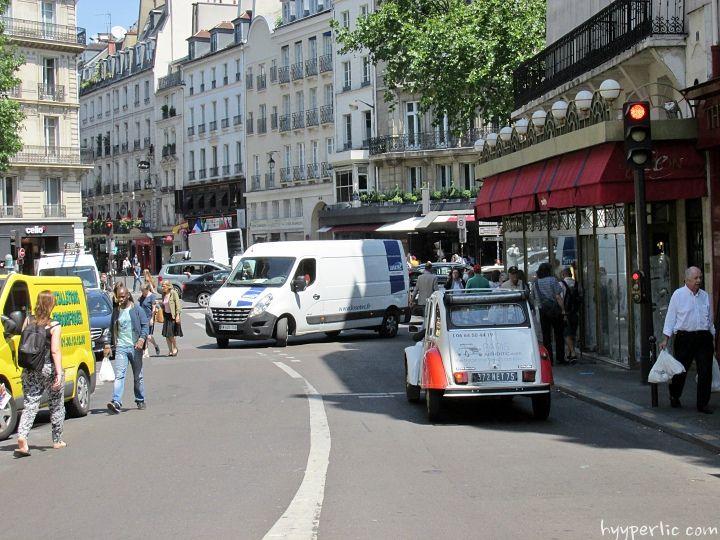 """Im Schatten der Bäume des Champ de Mars in Paris stehend höre ich von weitem ein knatterndes Geräusch auf mich zukommen. In der Kulisse der beschleunigenden und bremsenden Autos rund um den berühmten Eiffelturm höre ich sie deutlich heraus, die Citroen 2CV """"Ente"""". Der Fahrer steigt rasch aus und entschuldigt sich für die Verspätung, derRead More"""