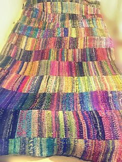 This blanket is made entirely from tubes knit from sock yarn, on an Addi circular machine. I just love how it looks, and it must be really warm! I think this would be a wonderful beginner project even on a flat bed machine with a ribber.