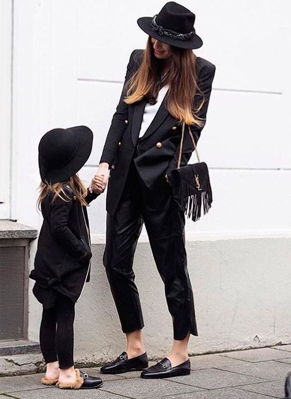 Mother daughter goals; Gucci loafers and slides, black white brim fedoras, black blazer with gold buttons, black trousers, YSL fringe handbag.