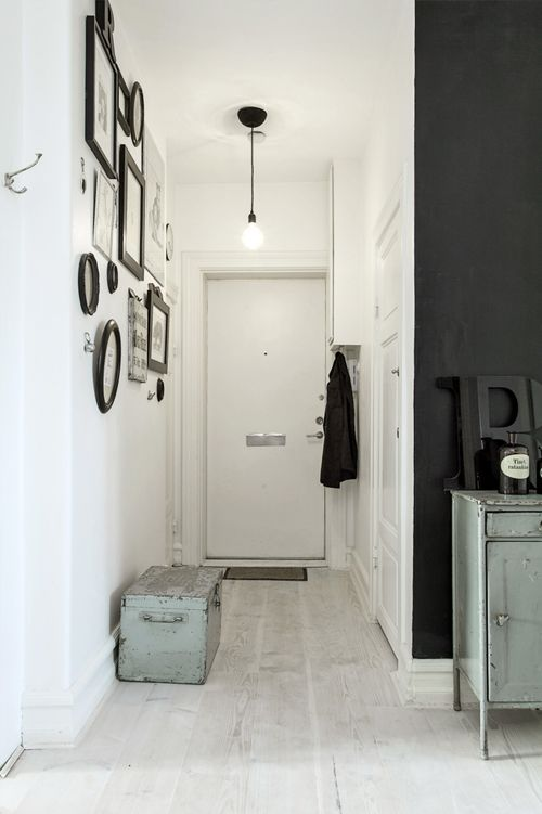 entry area staples: storage trunk, coat rack, doormat, light, and a wall of visually interesting objects