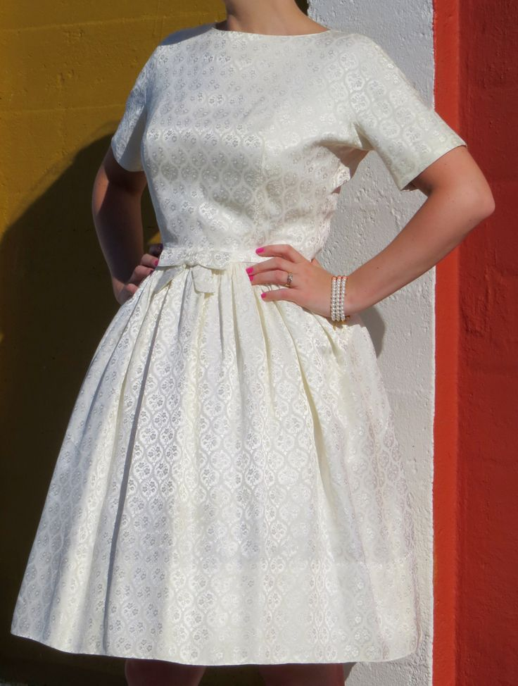 Short and sweet ivory brocade dress with beautiful button back detail and pretty bow at the centre front waist.