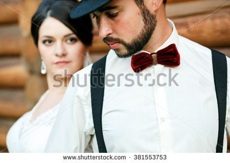 Thoughtful groom in hat with beard, mustache, bow tie and suspenders. Bride in white wedding dress. Stylish couple standing near wall of timber, looking away, close-up portrait. Gangster style.