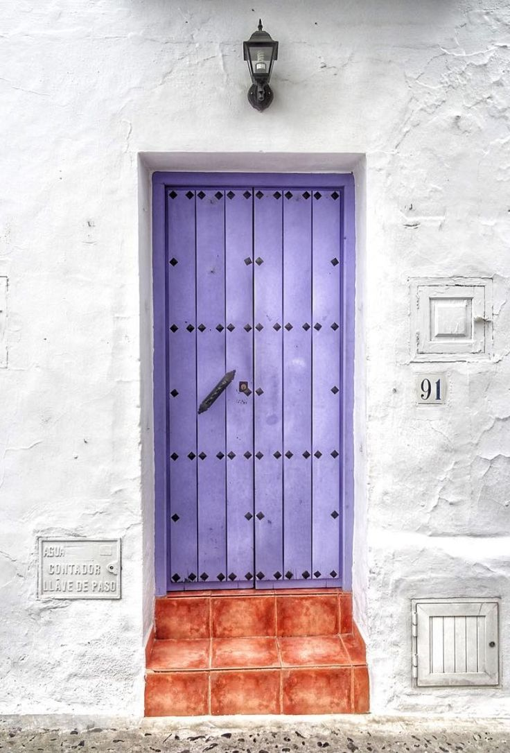 what a door. its like entarce into a mystical world. whit walls that purple door and the red brick steps that leads you there. What to join me? Frigiliana, Málaga, Spain