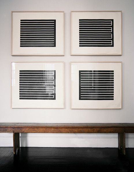 Minimalist Details Photo - A grid of framed black-and-white artwork above a wooden bench