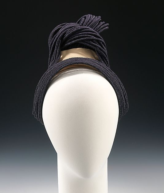 Straw hat, by Sally Victor, American, 1937. Victor often drew from cultures around the world for design inspiration, and was aided in that process by the staff of the Design Lab. This example of that practice also incorporates unconventional materials, another common element in Victor's designs. The tubular straw braid that literally looks like hair was the perfect expression for a design inspired by a hairstyle.