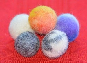 ullkulor tovade i tesil, felted balls of wool made with a tea-strainer.