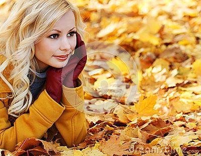 Ragazza bionda in Autumn Park con le foglie di acero. Modo bello