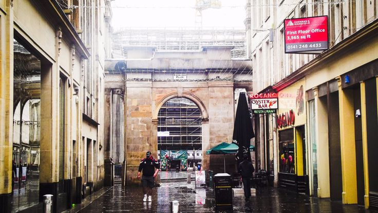 ROYAL EXCHANGE ON A WET MORNING By Catherine McGee  This photo just sums up how people had been feeling, Glasgow had non stop rain for months. It was a cold damp day and it was raining. This street photo just made me think about how others felt about the typical Scottish weather it was supposed to be spring time but felt like a cold winters day.