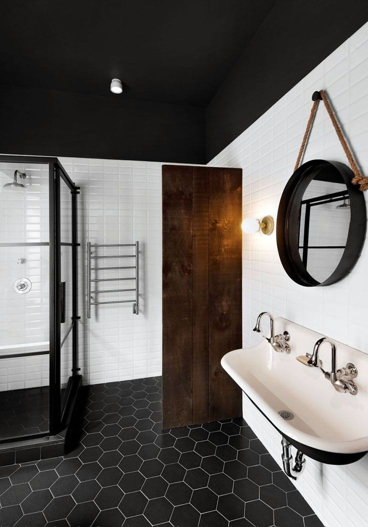 8 Examples Of Tile Flooring With Geometric Patterns // This bathroom uses simple black hexagonal tiles to create a modern and dramatic geometric floor.